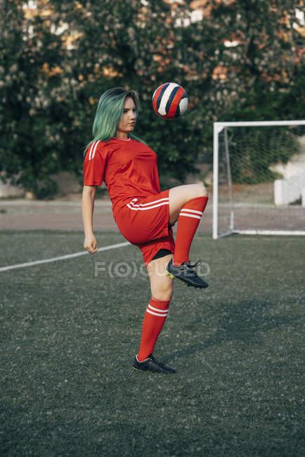 Junge Frau beim Fußballspielen auf dem Bolzplatz beim Balancieren — Stockfoto