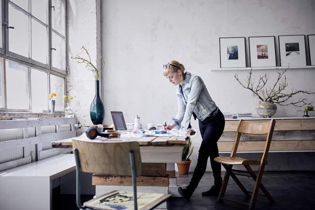 Donna che lavora alla scrivania nel design loft — Foto stock