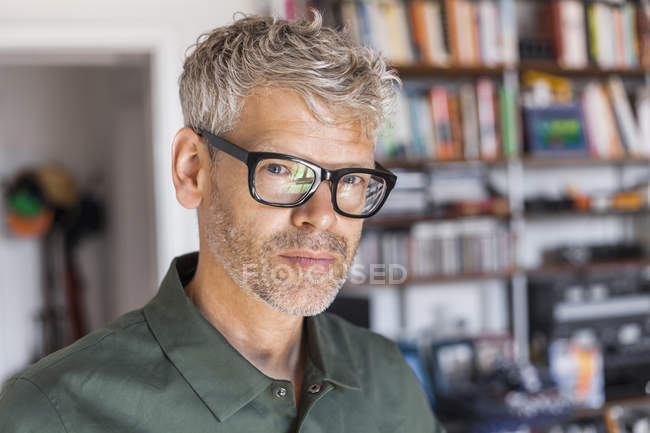 Portrait of mature man with grey hair and stubble wearing glasses at home — Stock Photo