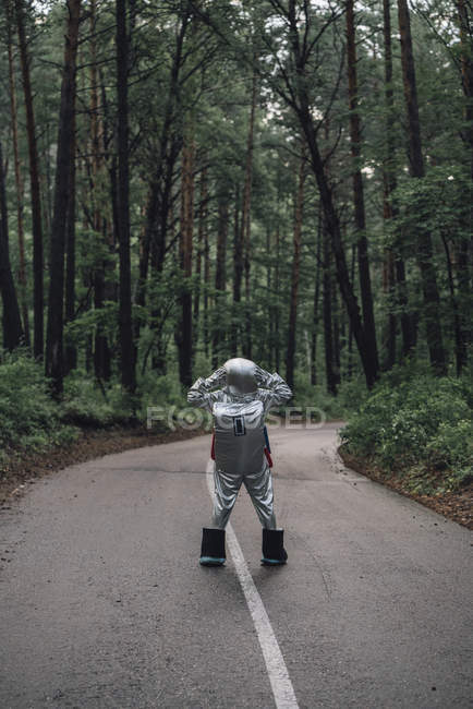 Spaceman exploring nature, standing on road in forest — Stock Photo