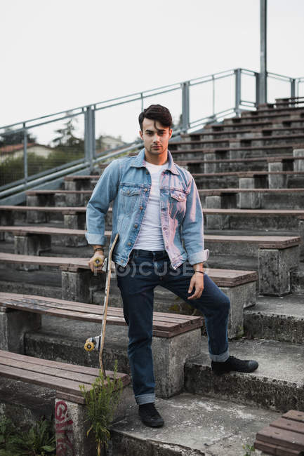 Portrait of young man with skateboard on bleachers — Stock Photo
