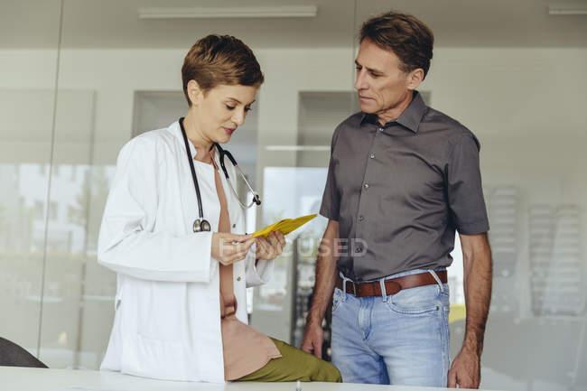 Женщина смотрит на карточку обезболивания встревоженного пациента — стоковое фото