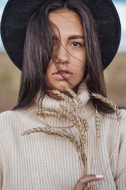 Retrato da mulher nova com as orelhas do chapéu desgastando do trigo e do pulôver do gola — Fotografia de Stock
