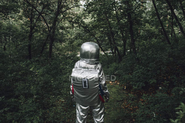 Spaceman exploring nature, walking in green forest — Stock Photo