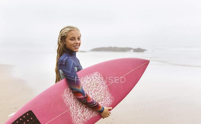 Молодая серфингистка держит доску для серфинга на пляже — стоковое фото
