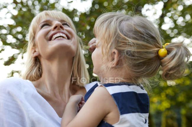 Щаслива мати носила на вулиці свою доньку. — стокове фото
