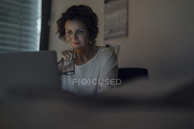 Businesswoman working overtime, using laptop, holding glasses — Stock Photo