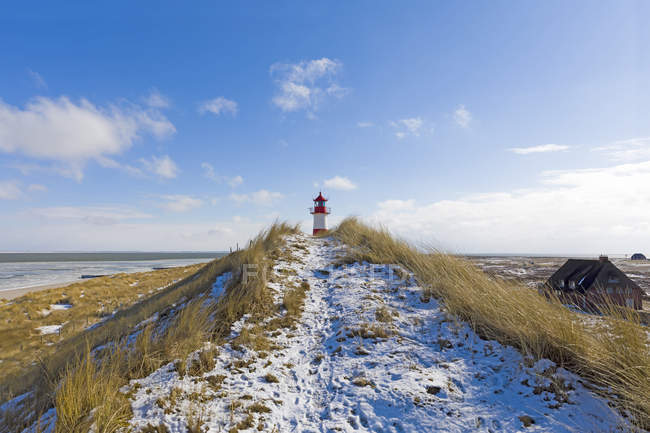 Germany, Schleswig-Holstein, Sylt, beach, dune and lighthouse in winter — Stock Photo