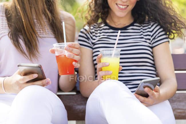 Primer plano de dos amigas sentadas en un banco con slush y teléfonos celulares - foto de stock