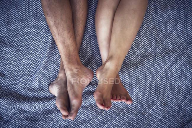 Piernas descalzas de pareja joven, acostado en la manta de la cama - foto de stock