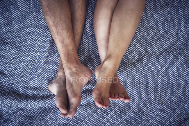 Barefoot legs of young couple, lying on bed blanket — Stock Photo