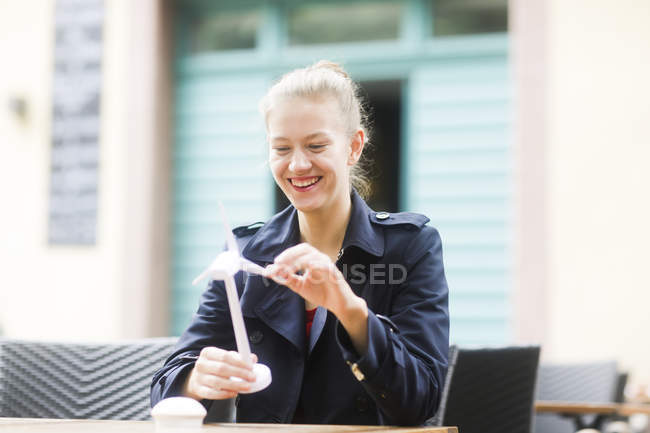 Portrait of laughing blond woman looking at model of wind turbine — Stock Photo