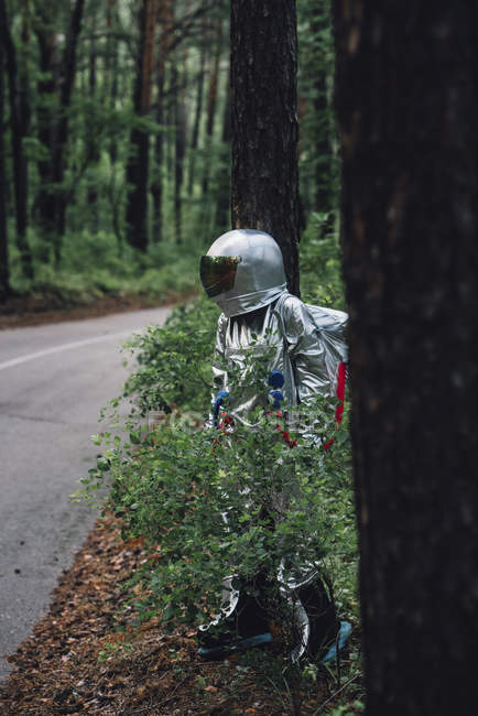 Spaceman hiding behind foliage at road in forest — Stock Photo