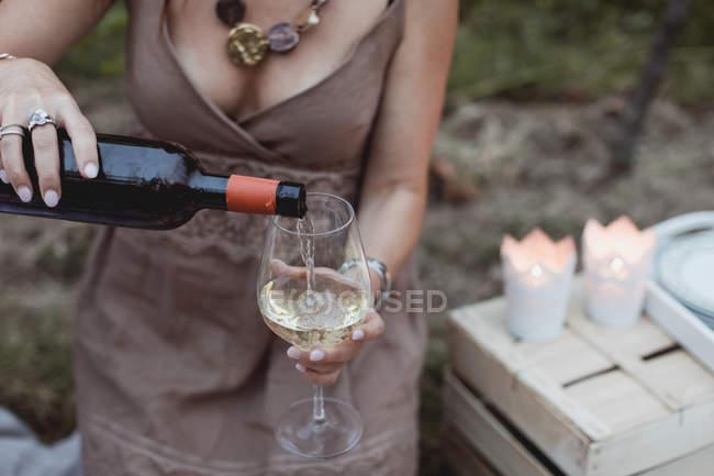 Женщина наливает вино в бокал на пикник на природе — стоковое фото