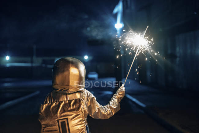 Rear view of spaceman standing outdoors at night and holding sparkler — Stock Photo