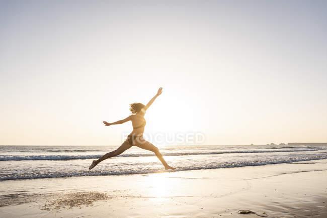 Молодая женщина, прыгающая от радости на пляже на закате — стоковое фото