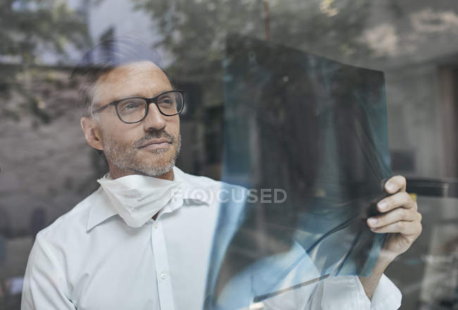Портрет радиолога за оконным стеклом, смотрящего на рентгеновское изображение — стоковое фото