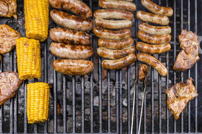 Different meat, maize and fried sausages on barbecue grill — Stock Photo