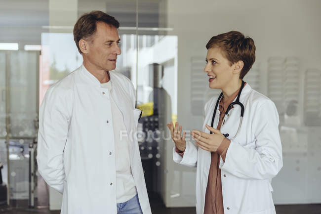 Two confident doctors standing in practice, discussing — Stock Photo