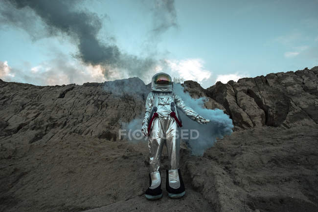 Abandoned spaceman giving smoke signals in desert — Stock Photo