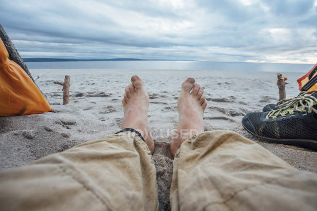 Barefoot man, lying on beach at sea water — Stock Photo