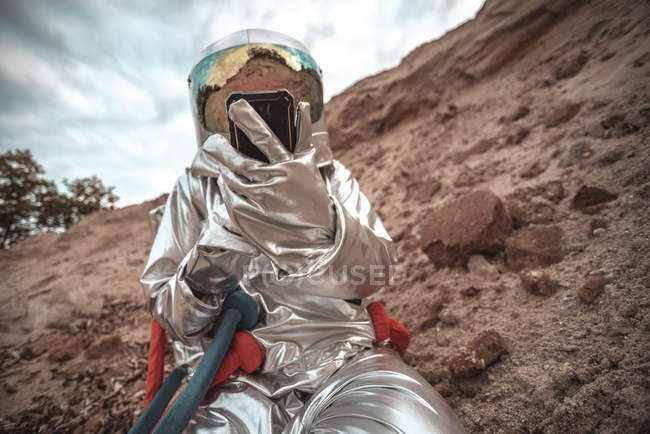 Spaceman examining new planet, using smartphone — Stock Photo