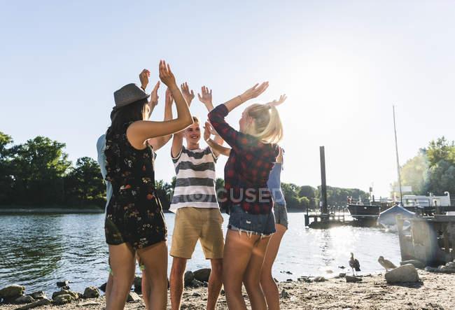 Grupo de amigos que levantam suas mãos no beira-rio — Fotografia de Stock
