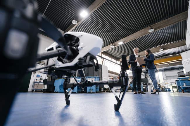 Empresario y compañero de trabajo discutiendo la producción de drones - foto de stock