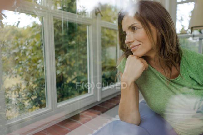 Femme mûre souriante sur le canapé à la maison regardant par la fenêtre — Photo de stock