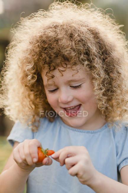Retrato de menina rindo com tomate — Fotografia de Stock