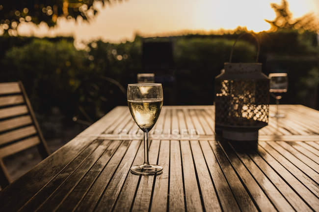 Glass of white wine on table at sunset — Stock Photo