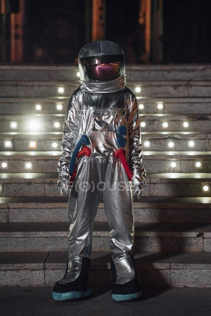 Spaceman standing at illuminated stairs at night — Stock Photo