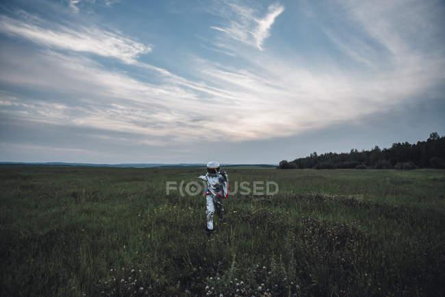 Spaceman exploring nature, walking in meadow — Foto stock