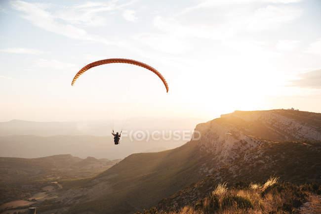 Spagna, Silhouette di parapendio svettante in alto sopra le montagne al tramonto — Foto stock