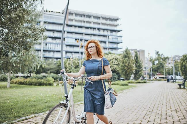 Giovane donna che cammina nel parco, spingendo la bicicletta — Foto stock