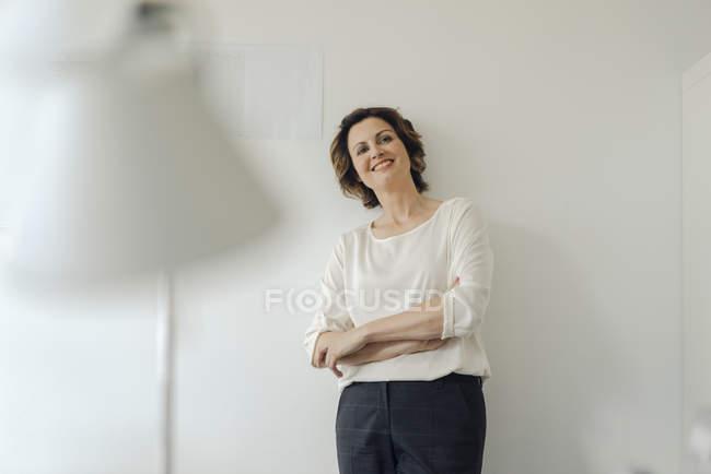Geschäftsfrau lehnt im Büro mit verschränkten Armen an Wand und lächelt — Stockfoto