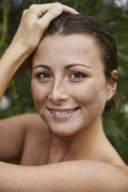 Portrait of smiling young woman with freckles in nature — Stock Photo