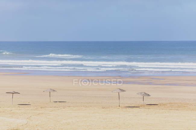 Marocco, spiaggia vuota, ombrelloni di paglia — Foto stock