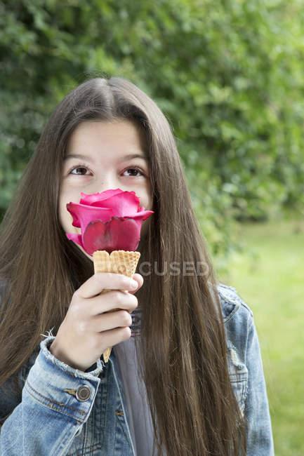 Девочка, пахнущая розовой розой в конусе мороженого — стоковое фото