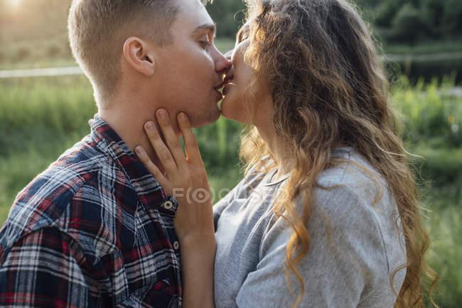 Романтическая пара целуется на закате на природе — стоковое фото
