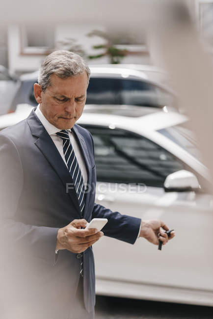 Businessman checking message while using remote control key of car — стокове фото