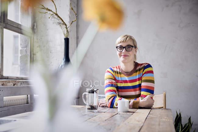 Retrato de mulher sorridente sentada com xícara de café em design loft — Fotografia de Stock
