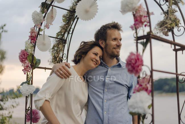 Pareja feliz abrazando bajo arco de boda - foto de stock