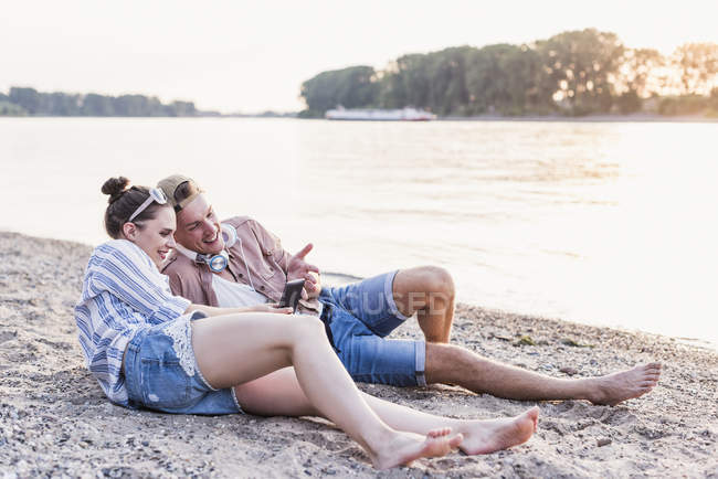 Young couple relaxing at riverbank and sharing smartphone — Stockfoto