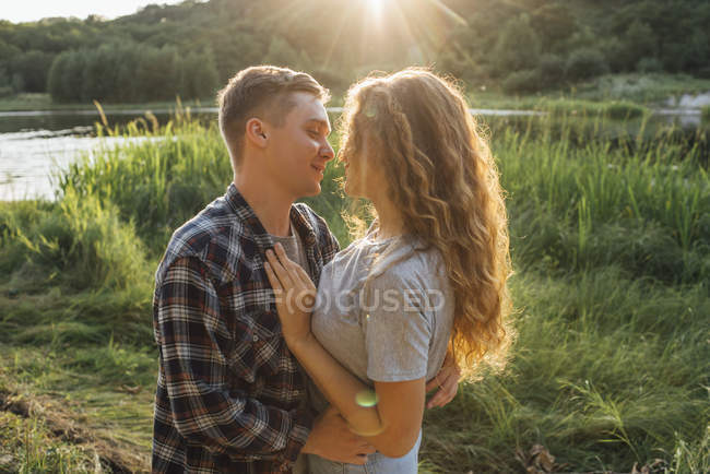 Romantic couple kissing in nature at sunset — Stock Photo