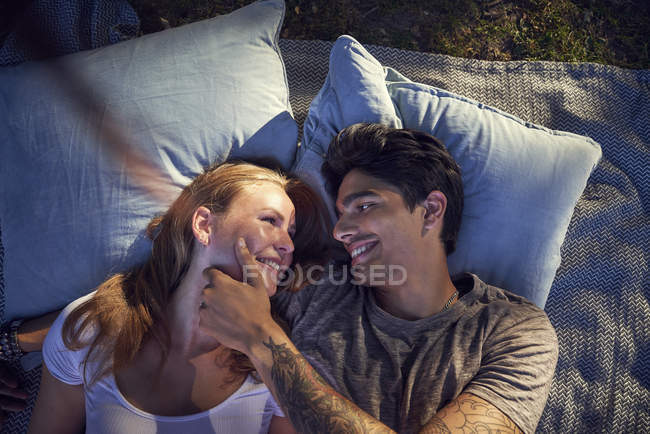 Young couple in love, lying on cushions on blanket on green grass — Stock Photo