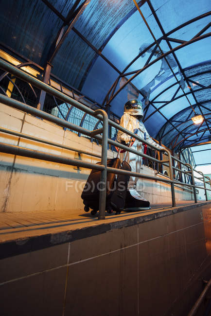 Spaceman in city at night standing with rolling suitcase — Stock Photo