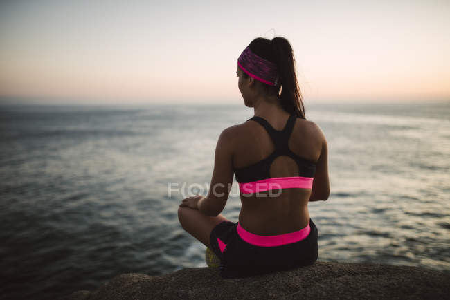 Femme sportive assise sur un rocher, face à la mer le soir — Photo de stock