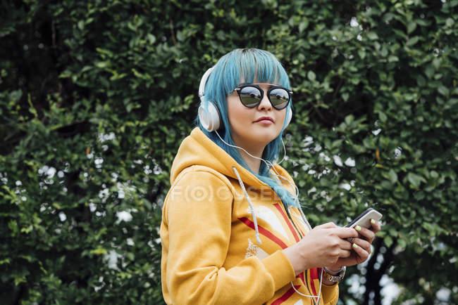 Портрет молодой женщины с голубыми волосами, слушающей музыку со смартфоном и наушниками — стоковое фото