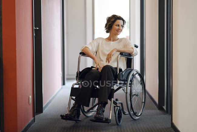 Інваліди ділової жінки сидять на інвалідному візку в офісі і дивиться — стокове фото